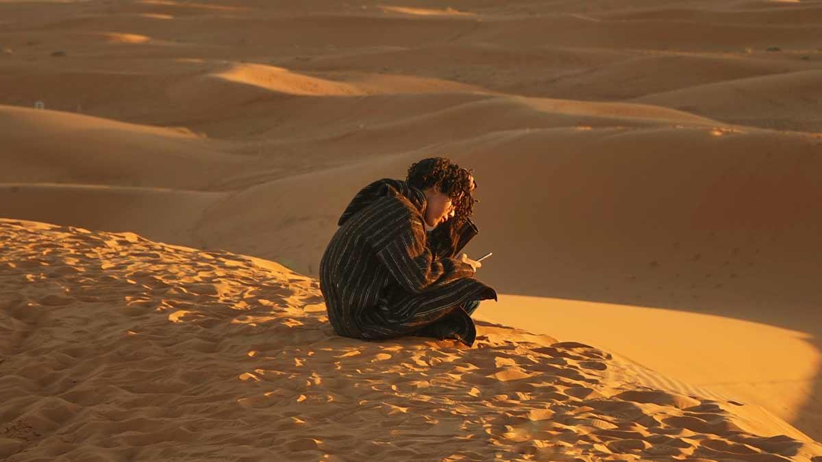Symbolfoto: Junger Mann mit Telefon in der Wüste
